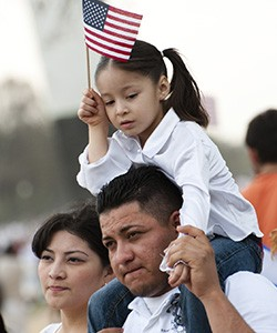 Young child in white shirt on dad's shoulders next to mom waiving an American Flag - Immigrant Family
